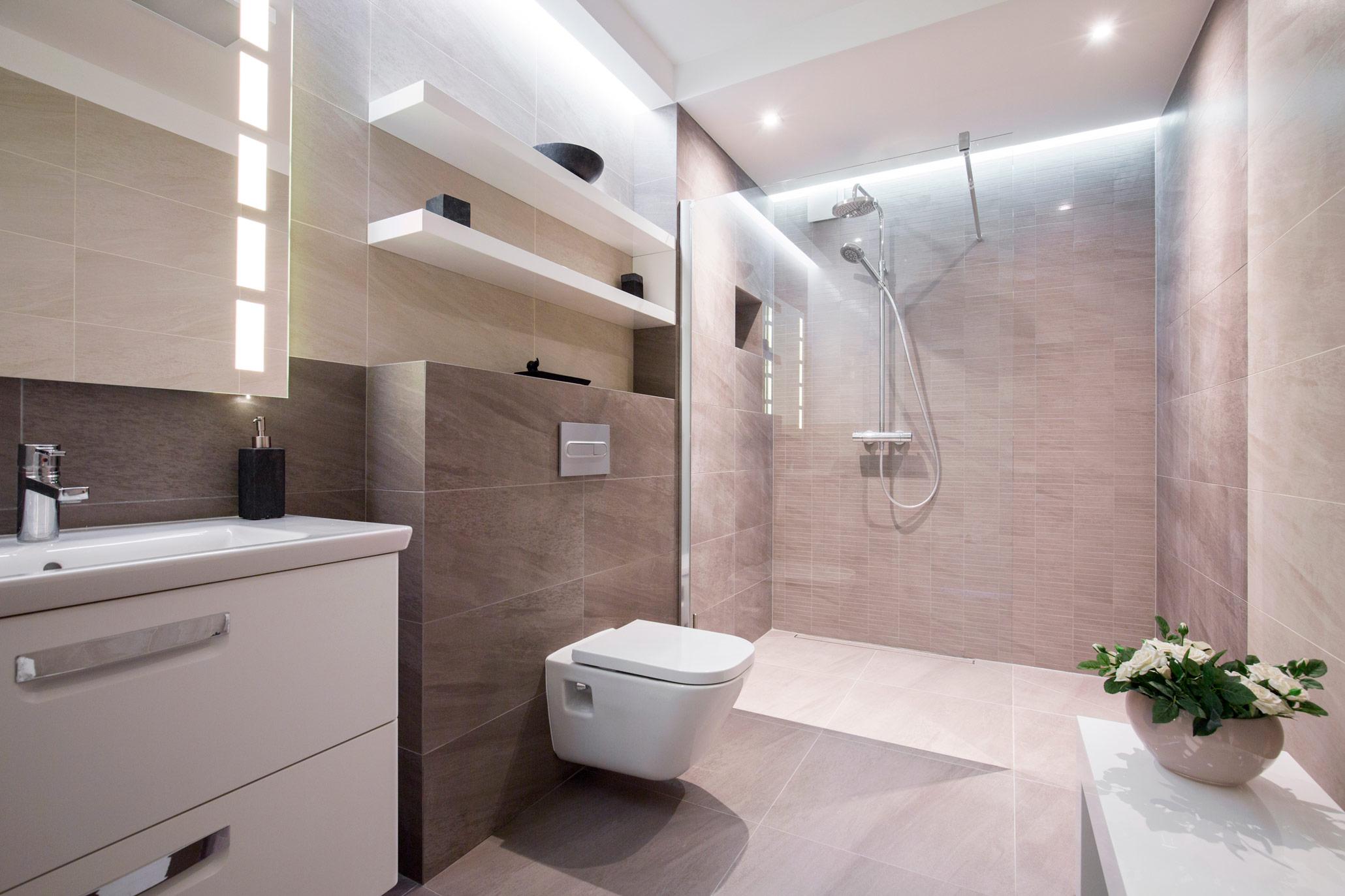 Bad med vask, toalett og dusj og fine fliser